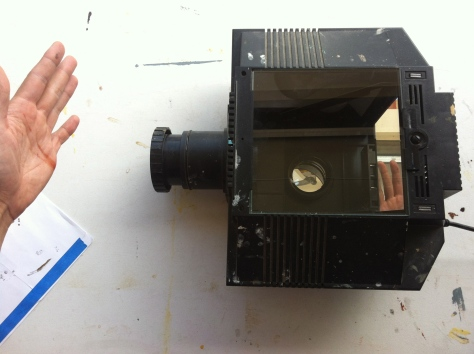 Maybe you remember overhead projectors from school? This works the same way, except you don't have to use transparencies, you can use opaque paper as well.
